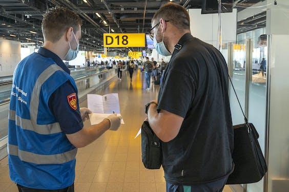 SCHIPHOL - Medewerkers van de GGD ondervragen reizigers op luchthaven Schiphol. Reizigers uit risicogebieden worden achter de douane gecontroleerd op coronaklachten. ANP EVERT ELZINGA