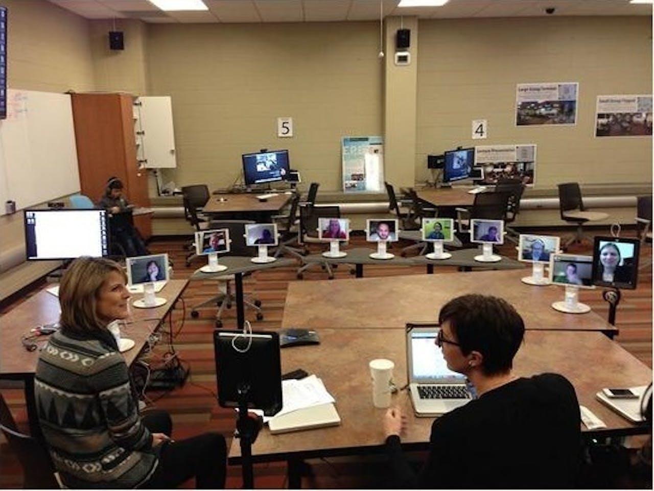 Een klas vol robots. Elke student kan zelf de richting van zijn scherm bepalen. Zo kunnen zij de docent of juist elkaar aankijken.