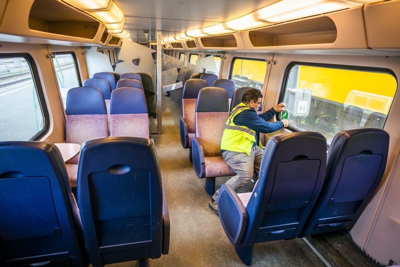 Een monteur van de NS plakt stickers in een trein