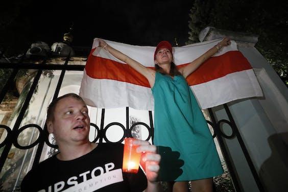 Burgers protesteren met een vlag voor de ambassade van Rusland in Minsk.