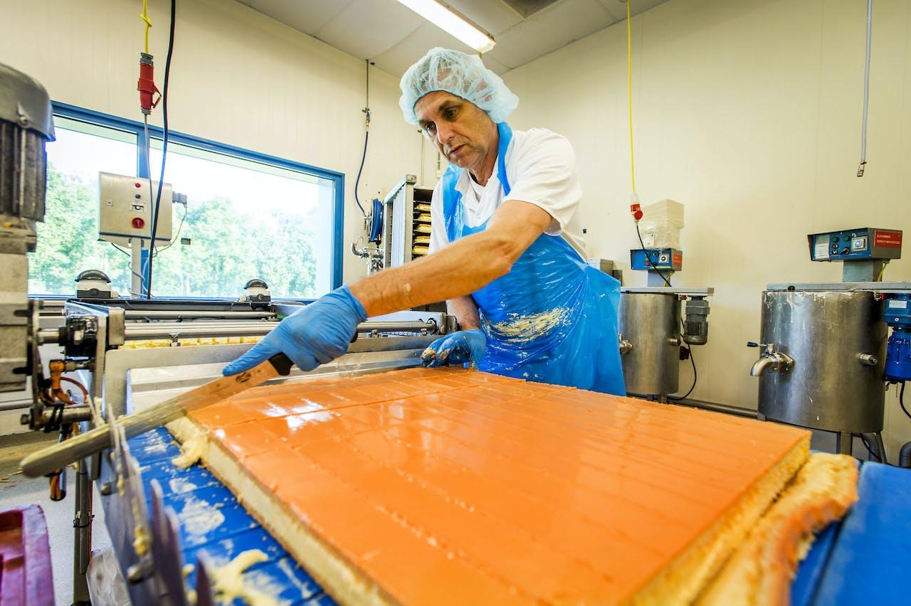De productie van oranje tompoucen in de Hema-bakkerij in Almere.