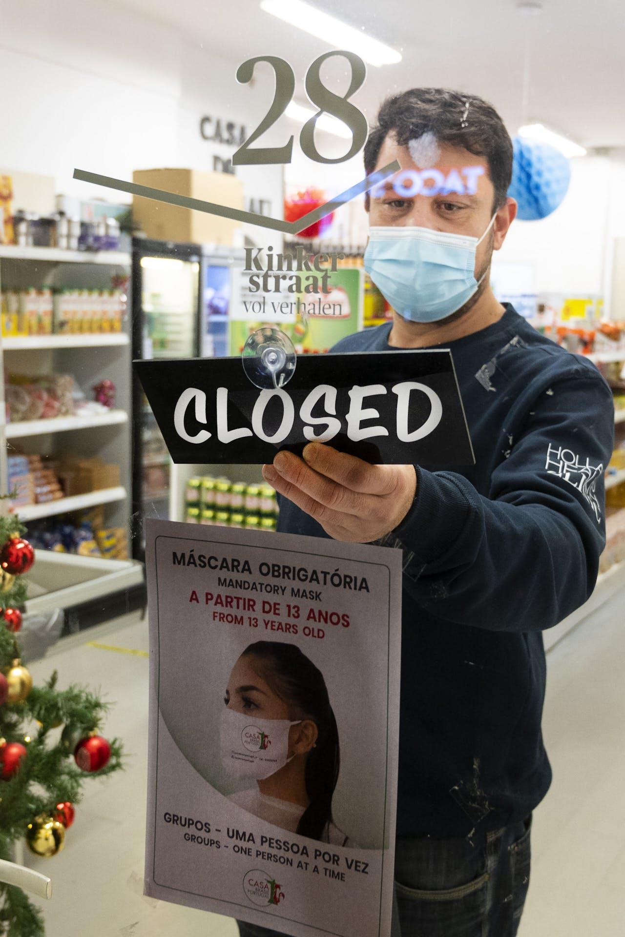 Een winkelier sluit zijn zaak.