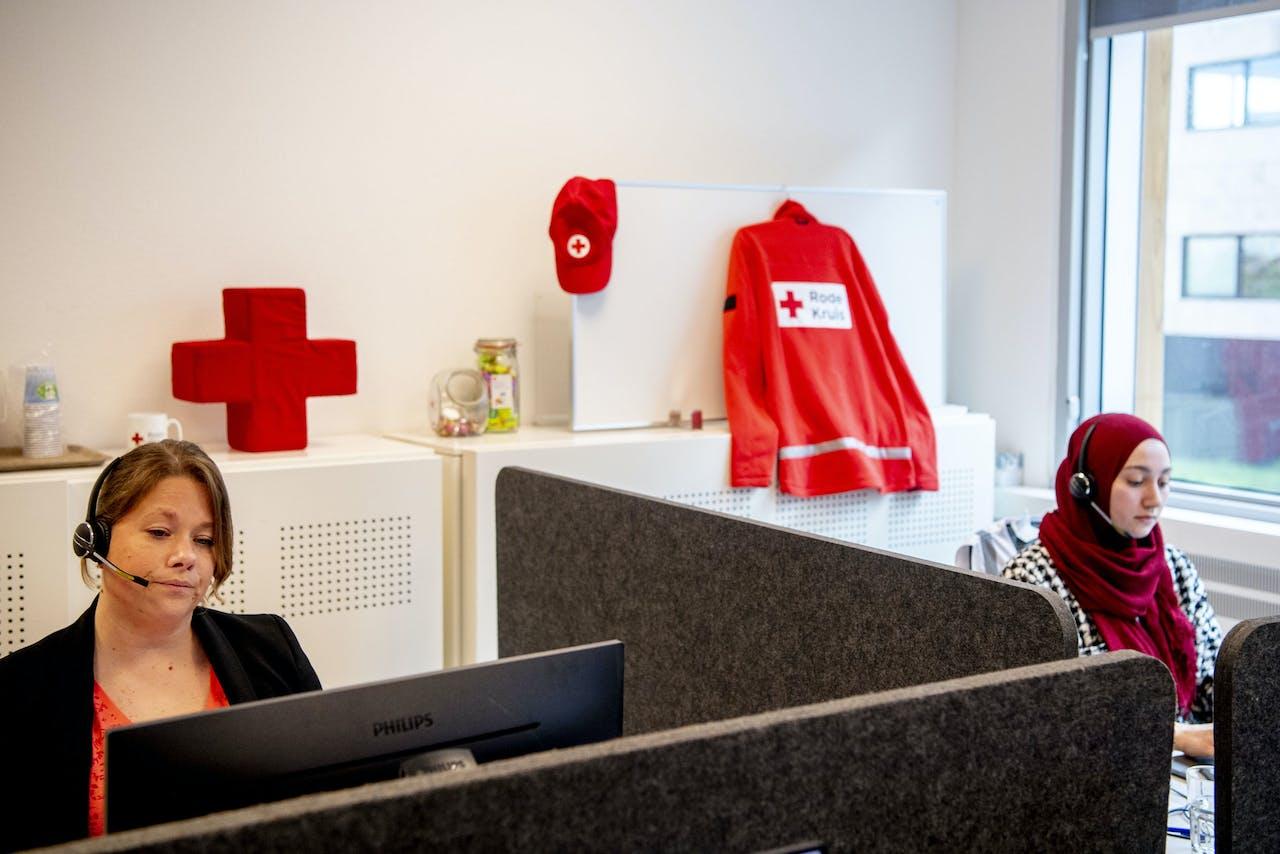 Een medewerker van het Rode Kruis aan de telefoon.