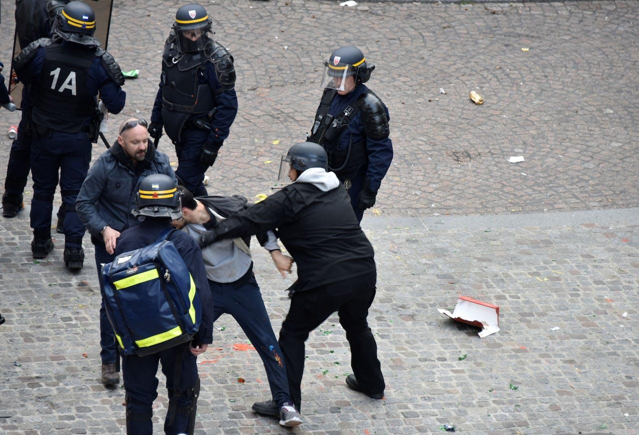 Macron's Chief Security Officer Alexandre Benalla (C) met politievizier en Vincent Crase (C, links), een beveiliger van Macron's partij, dragen een demonstrant weg tijdens protesten op 1 mei in Parijs.