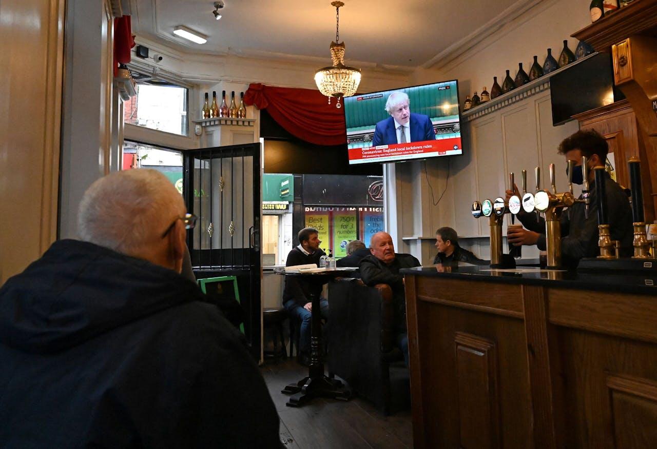 In een pub in Liverpool kijken klanten naar de speech van premier Boris Johnson.