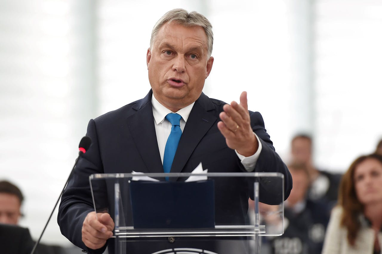 """Hungary's Prime Minister Viktor Orban gestures as he delivers a speech during a debate concerning Hungary's situation as part of a plenary session at the European Parliament on September 11, 2018 in Strasbourg, eastern France. Hungarian Prime Minister Viktor Orban vowed, on September 11, 2018, to defy EU pressure to soften his hardline anti-migrant stance, condemning what he called the """"blackmail"""" of his country. / AFP PHOTO / FREDERICK FLORIN"""