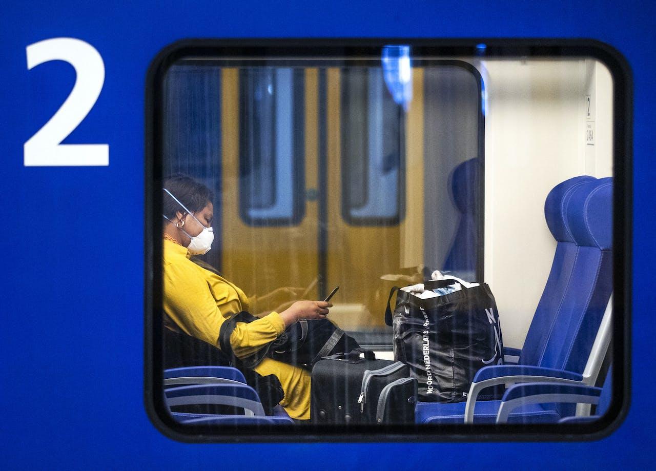 Een reiziger met een mondkapje op station Den Haag Centraal