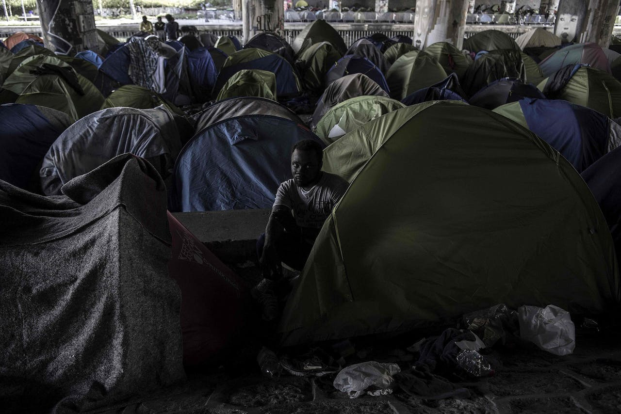 """2018-04-20 09:34:44 Burkina Faso's Aziz Porogo, a 28-year-old migrant, sits in his tent at a makeshift camp set under a bridge near Porte de la Villette, northern Paris on April 20, 2018. Aziz left Burkina Faso in 2009 as he could not find a job in his impoverished home country. Like many African migrants back then, he traveled to Libya where he worked until 2011 and the uprising which led to the death of then leader Colonel Muammar Gaddafi. The following weeks of unrest prompted Aziz to head to Europe, embarking on a boat he says was packed with some 1,400 people and which took him to Lampedusa in southern Italy. After working a few years in Italy, Aziz reached France at the end of 2017, ultimately landing at this tent camp in Paris. """"When I send pictures of the camp to my family, they do not believe I'm in France but assume I'm still in Libya"""", Aziz says when asked about the living conditions along the canal Saint-Denis. / AFP PHOTO / CHRISTOPHE ARCHAMBAULT"""