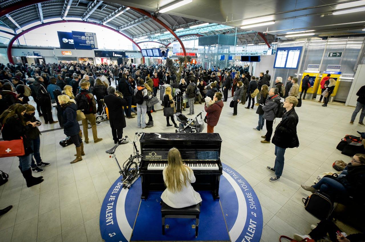 De stationspiano kan ook voor verlichting zorgen als het even niet meezit: door een storing kwamen deze reizigers vast te zitten op Utrecht CS.