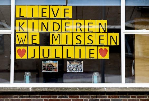 """2020-04-02 10:58:58 ROTTERDAM - De tekst """"Lieve kinderen we missen jullie"""" hangt voor een raam bij een school in Rotterdam. De scholen zijn tot minstens 28 april gesloten, als een van de maatregelen omtrent het coronavirus. ANP KOEN VAN WEEL"""