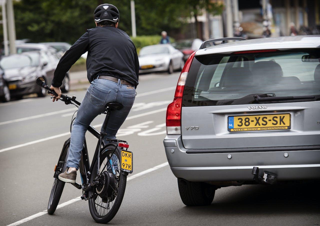 Een fietser op een e-bike neemt deel aan het verkeer op een kruispunt in Den Haag.