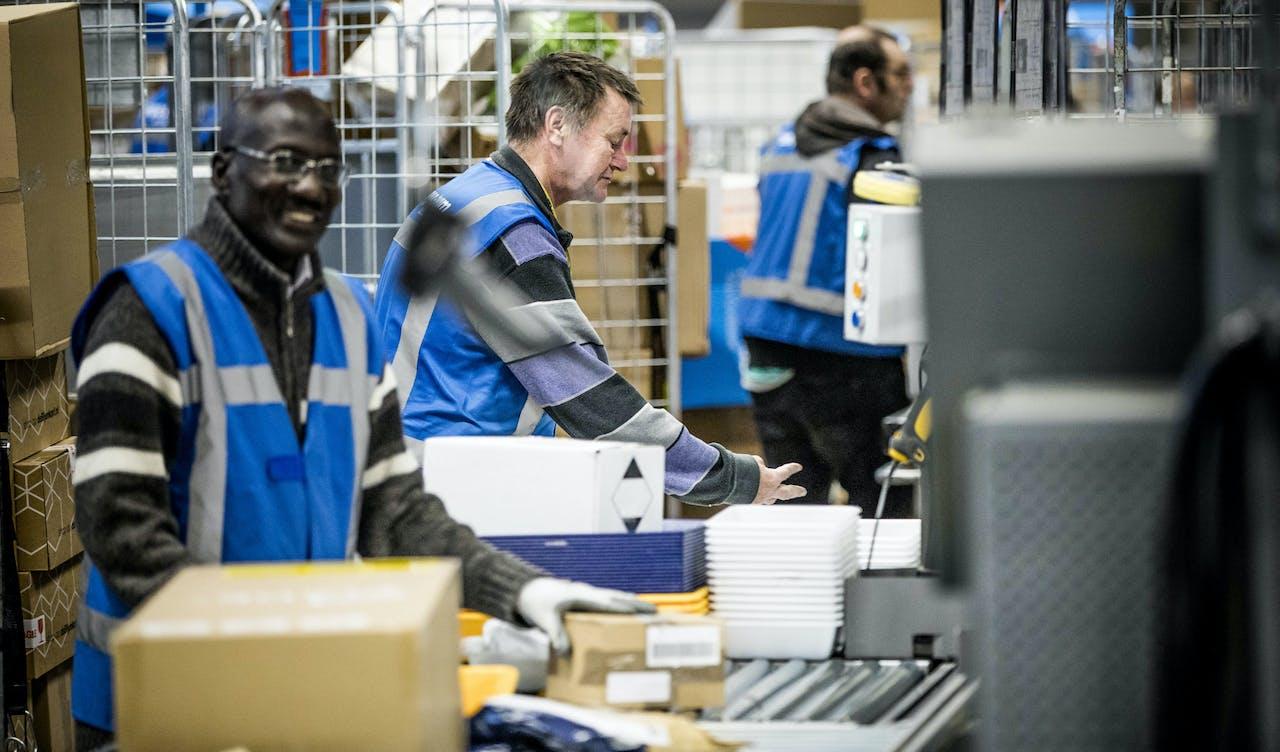 Medewerkers van PostNL sorteren pakketjes in het sorteercentrum in Nieuwegein.