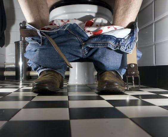 Een man zit op het toilet.