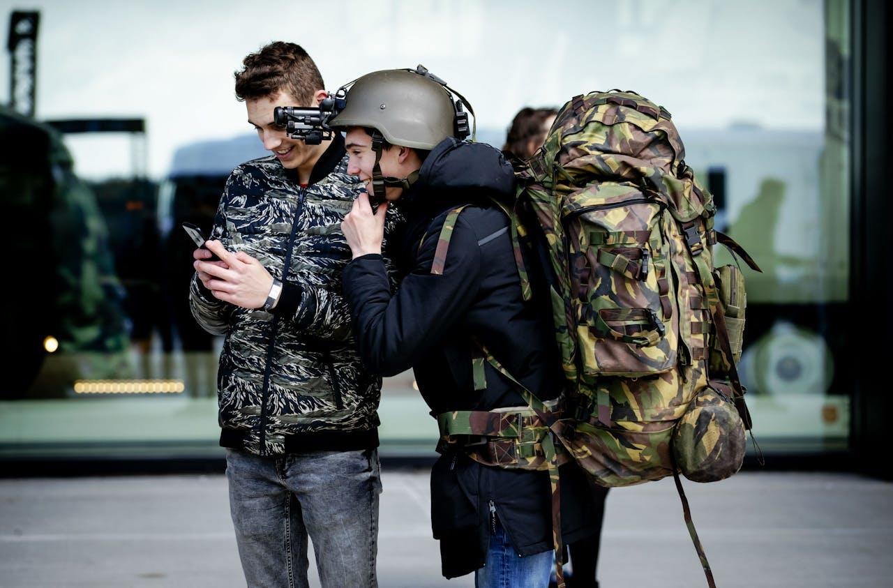 Een bezoeker probeert een zware bepakking een een nachtbril. Defensie organiseerde samen met partners uit het onderwijs en het bedrijfsleven het tech-event DEFLAB in het Nationaal Militair Museum met als doel technisch talent te werven.