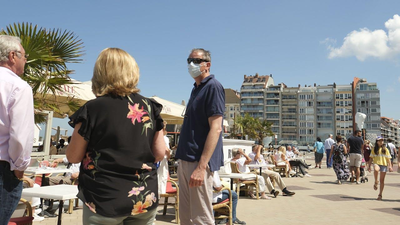 Toeristen met mondkapjes op aan het strand van Knokke-Heist.
