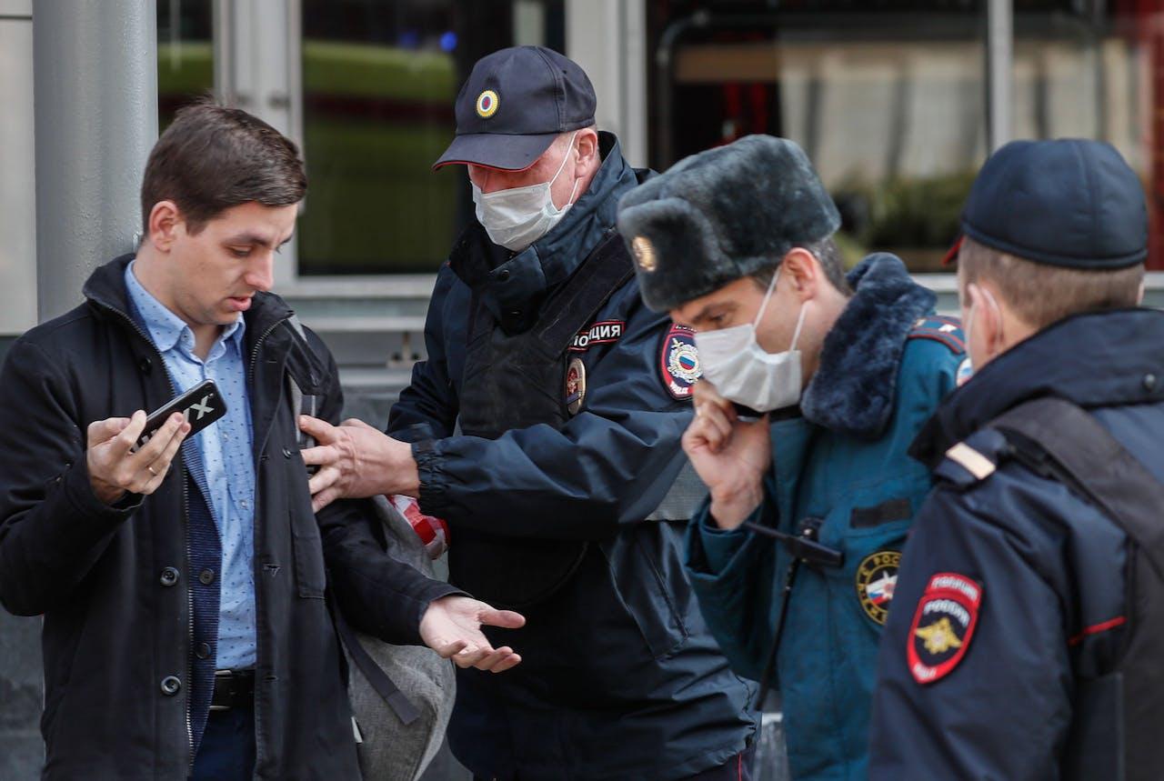 De Russische politie houdt een man aan die zich niet aan de coronaregels zou hebben gehouden.