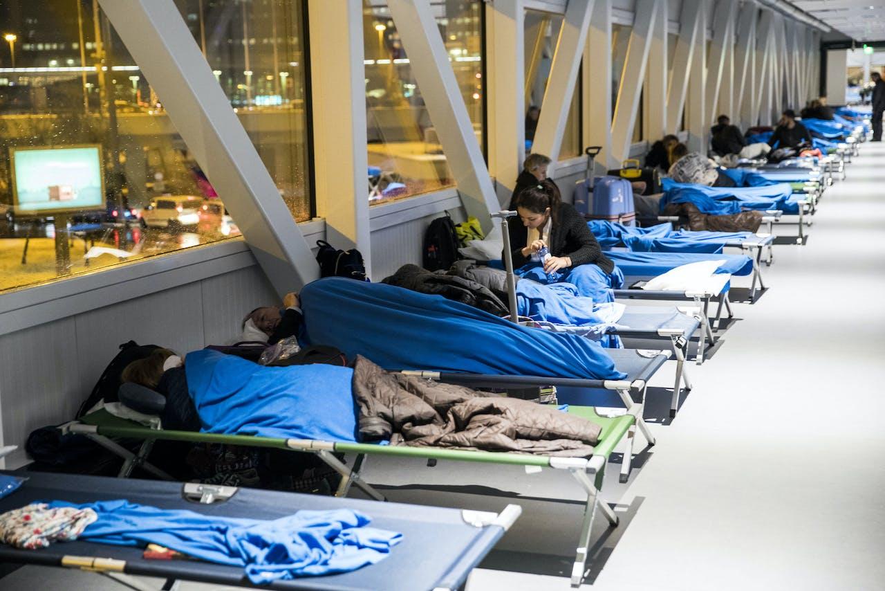 11 december 2017: Gestrande reizigers brengen op Schiphol de nacht door op veldbedden.