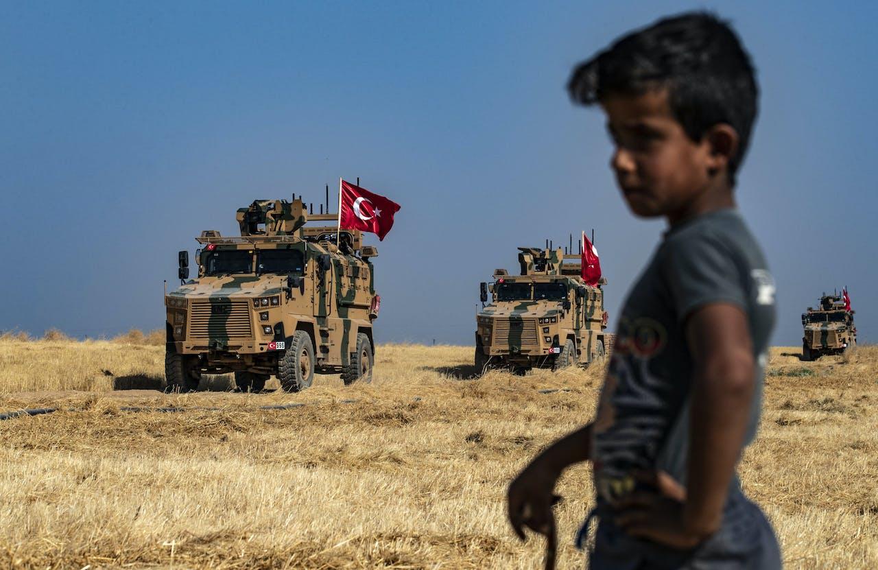 Een jongen kijkt toe terwijl Turkse militaire voertuigen, die onderdeel zijn van een Amerikaans konvooi, deelnemen aan een Amerikaanse patrouille aan de rand van Tal Abyad langs de Turkse grens.
