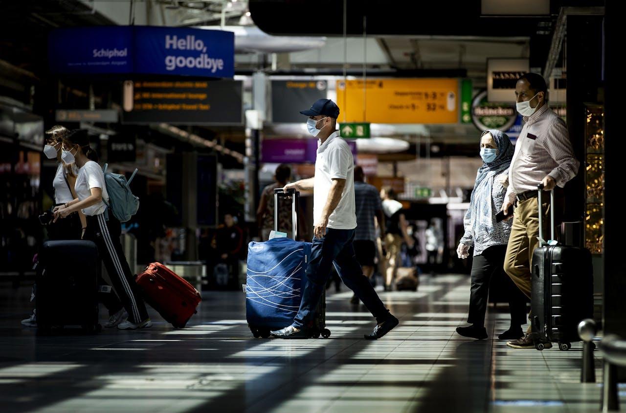 Reizigers met mondkapjes op luchthaven Schiphol.