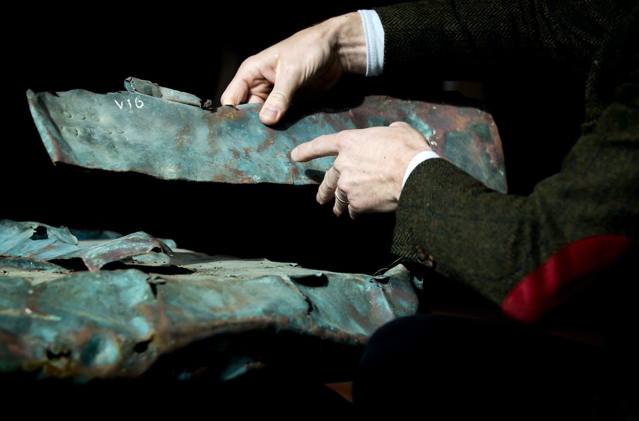 Koperplaten bij de presentatie van een archeologische vondst. Eeuwenoud koper en hout is afkomstig uit een scheepswrak uit 1536, dat werd ontdekt tijdens de berging van containers van de MSC Zoe.