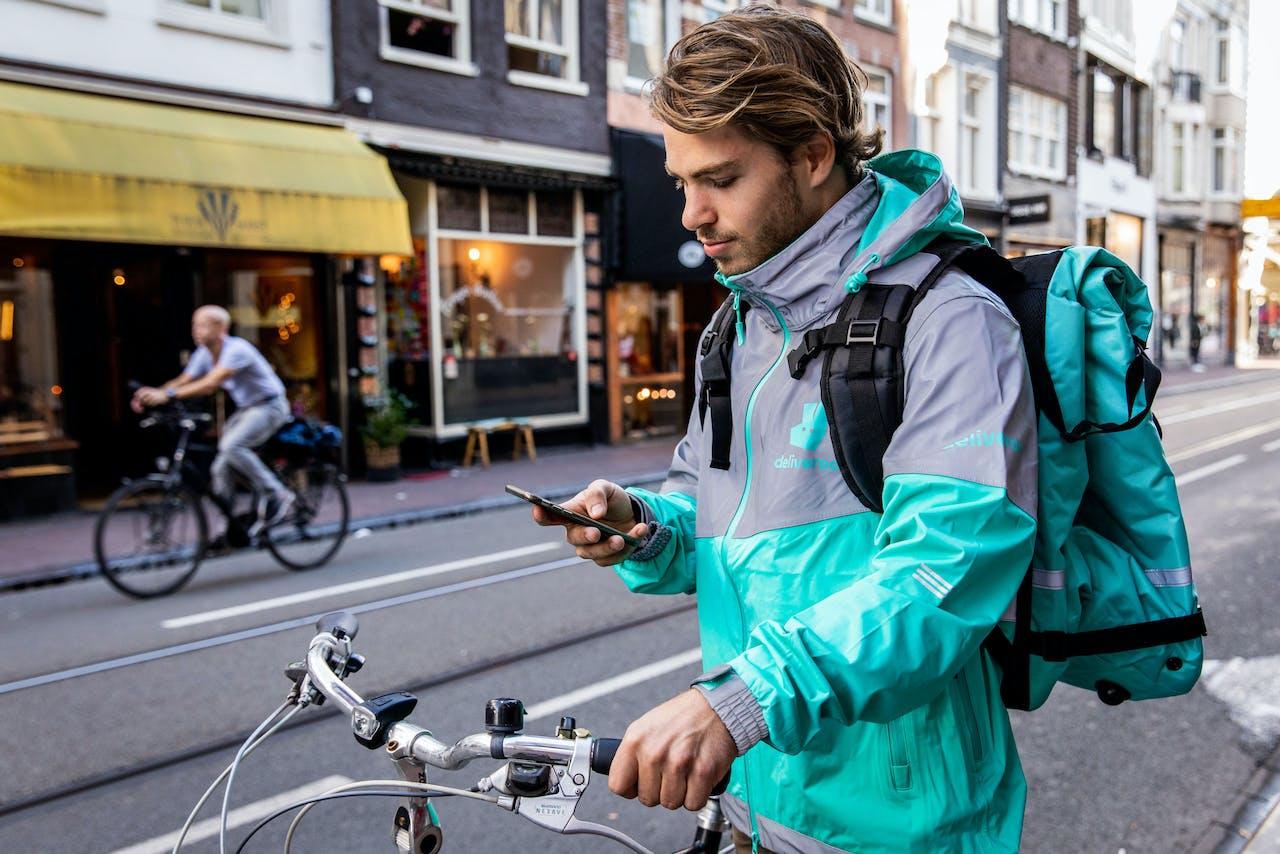 AMSTERDAM - Een bezorger van Deliveroo in het centrum van Amsterdam.