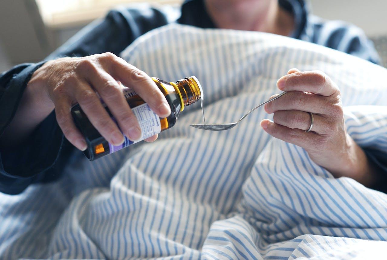 2012-10-17 00:00:00 ILLUSTRATIE - Een vrouw in bed neemt hoestdrank. ANP XTRA ROOS KOOLE