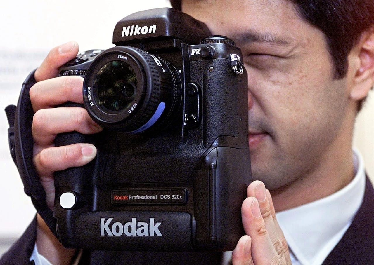 Een medewerker van Kodak demonstreert een digitale camera op een beurs in Tokio in 2000.