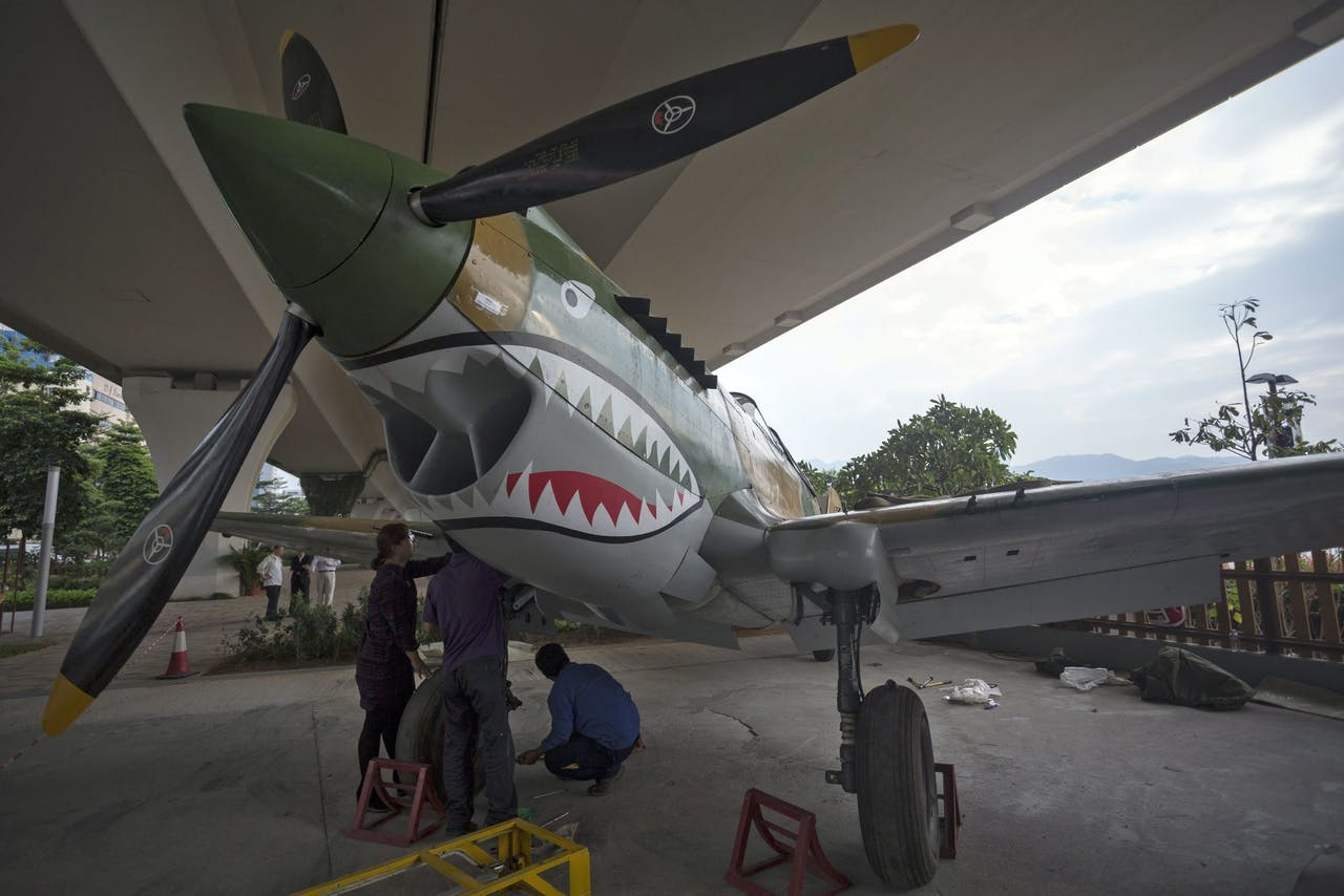 2015-11-04 16:57:18 epa05010359 Workers put together the replica of a Curtiss P-40 Warhawk showing the 'Flying Tigers' paint scheme in Hong Kong, China, 04 November 2015. The plane was brought in by the Hong Kong War History Research Association to be displayed until the end of November in commemoration of the 70th anniversary of the end of the World War II. EPA/JEROME FAVRE