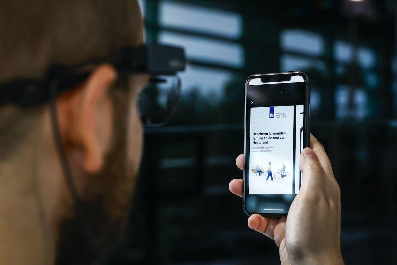 Studenten testen in een lab van de Universiteit Twente een coronawaarschuwingsapp die in opdracht van het kabinet wordt ontwikkeld.