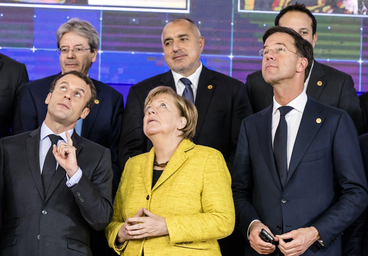 2017-12-14 19:09:27 BRUSSEL - (VLNR) De Franse president Emmanuel Macron, de Duitse Bondskanselier Angela Merkel en Premier Mark Rutte kijken naar een drone in de lucht tijdens de Europese Raad in Brussel. ANP BART MAAT
