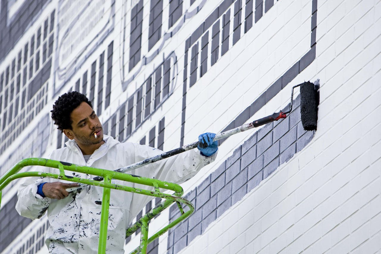 Graffiti-artiest Gais brengt graffiti aan op het NAI in Rotterdam. De Rotterdamse stichting Caramundo heeft tien Brazilianen opdracht gegeven om kunst aan te brengen op Rotterdamse muren.