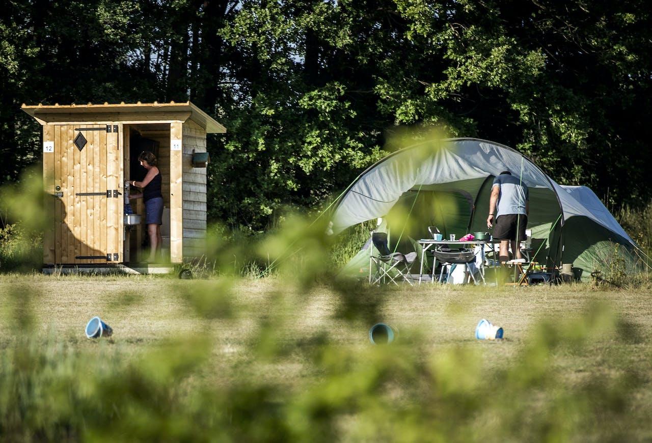 Een houten huisje met privé-sanitair bij de kampeerplek op een camping