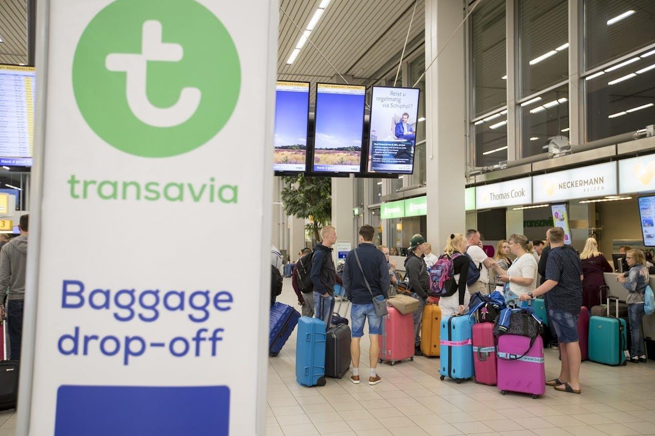 Reizigers wachten in een vertrekhal op luchthaven Schiphol.