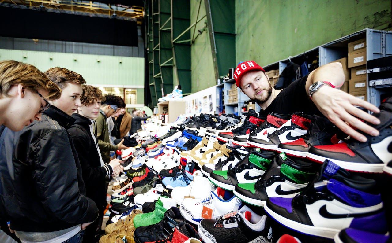 2018-12-02 14:03:35 ROTTERDAM - Bezoekers van Sneakerness bekijken de exclusieve en klassieke sneakers die op het event in de onderzeebootloods te koop zijn. ANP ROBIN VAN LONKHUIJSEN