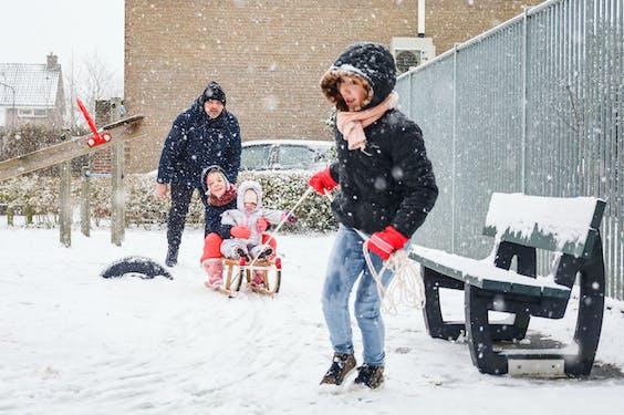 Kinderen op een slee in de sneeuw in Koudekerke.