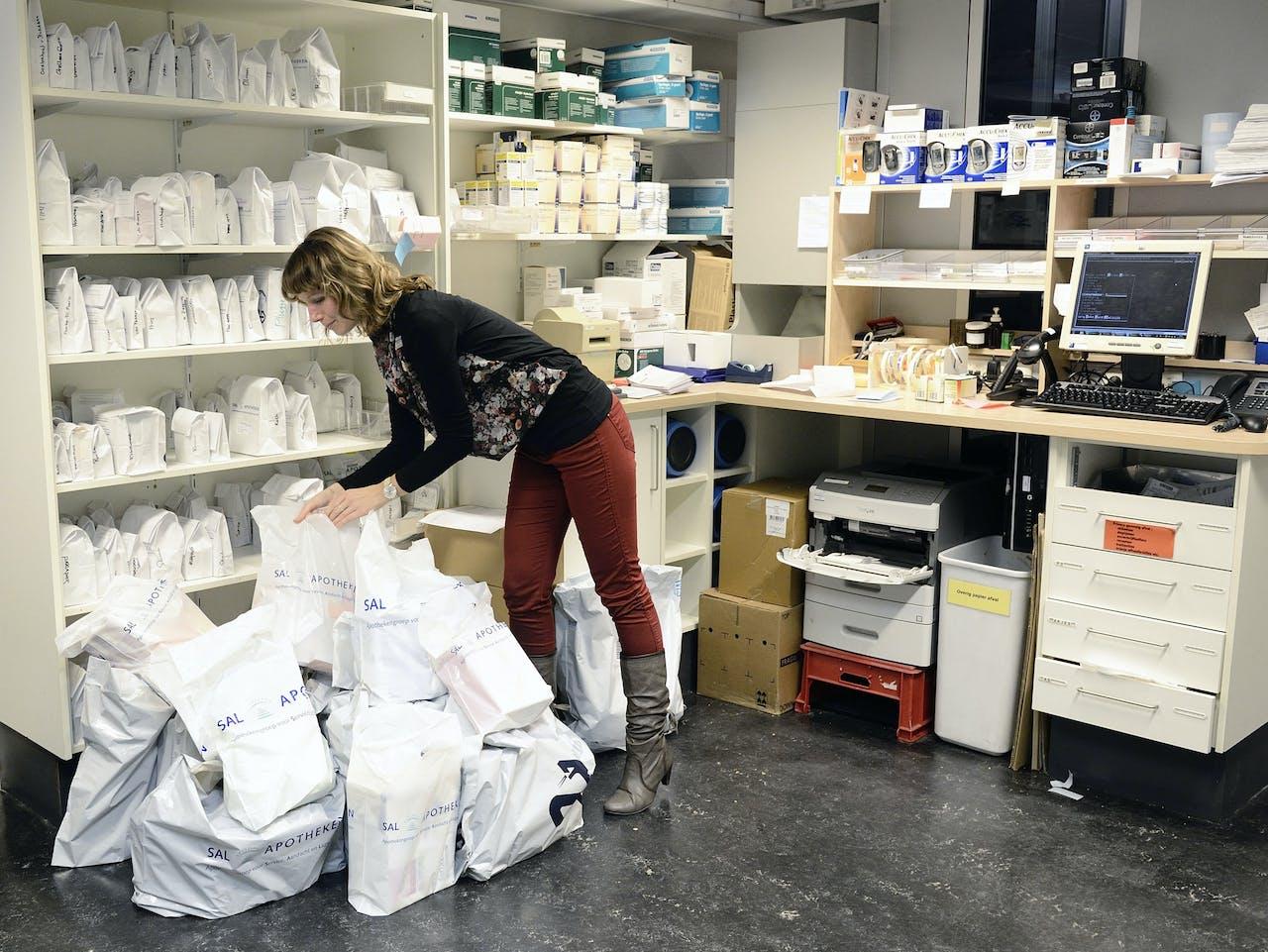 Illustratief beeld van een medewerkster van een apotheek die bestellingen gereed maakt.