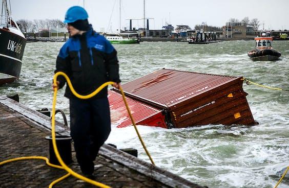 Een sleepboot brengt twee overboord geslagen containers van het schip MSC Zoe de haven binnen.