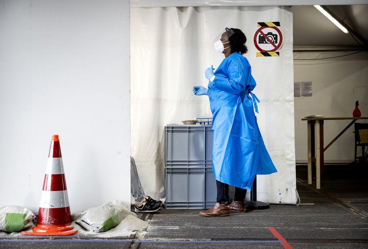 2020-07-29 11:27:19 ROTTERDAM - Een medewerker van de GGD Rotterdam-Rijnmond neemt een coronatest af in een teststraat. Het aantal besmettingen met het coronavirus blijft toenemen. In de regio Rotterdam-Rijnmond stijgt het aantal nieuwe patienten het meest. ANP KOEN VAN WEEL
