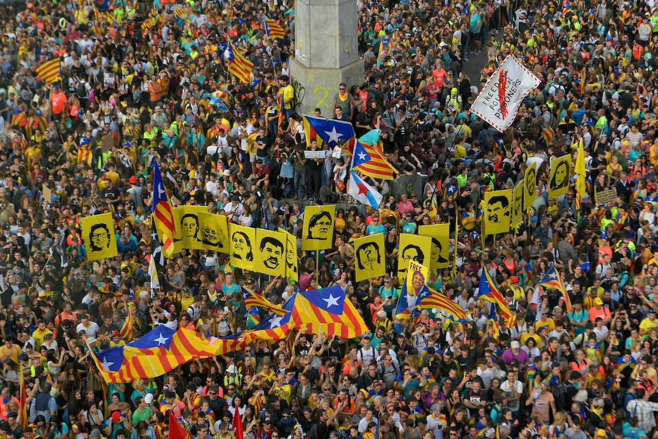 Mensen houden Catalaanse vlaggen en portretten van de separatistische leiders in de lucht tijdens de betoging op 18 oktober 2019.