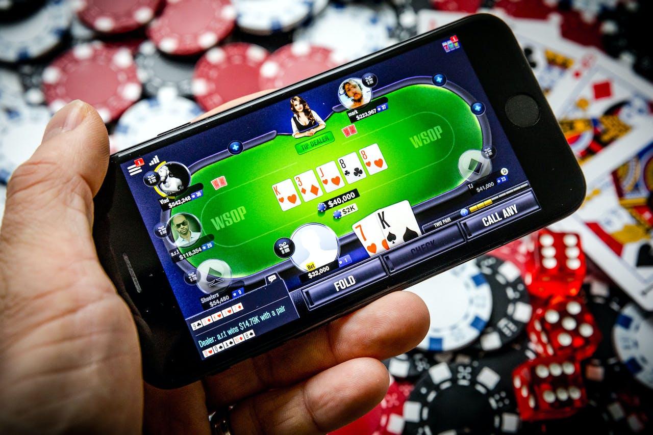 Een telefoon met een online pokerspel. Ruim 1,8 miljoen Nederlanders gaven in 2018 aan weleens tegen betaling een online kansspel te spelen.