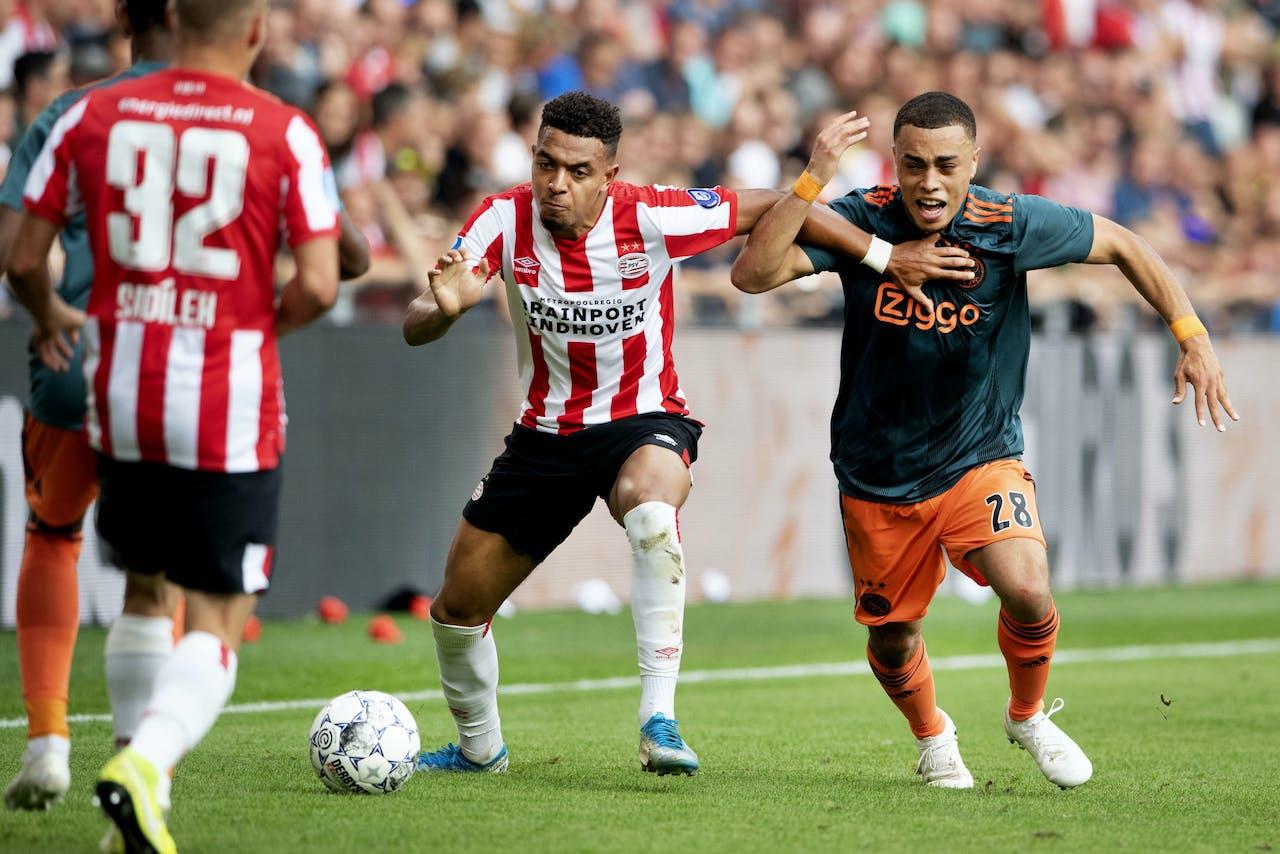Donyell Malen van PSV in duel met Sergino Dest van Ajax. PSV speelt in de eredivisie met 1-1 gelijk tegen Ajax.