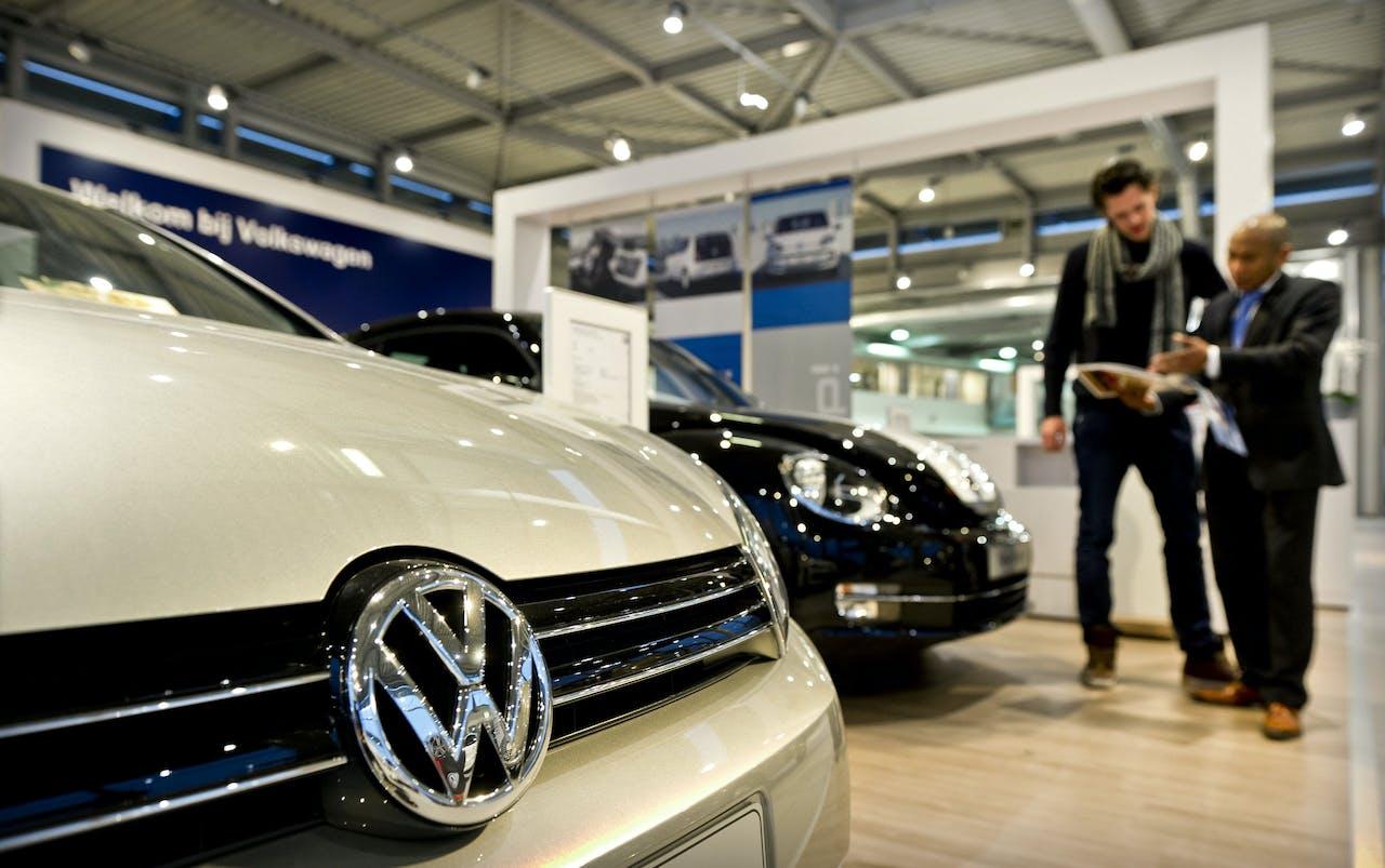 Een klant krijgt uitleg bij een VW dealer