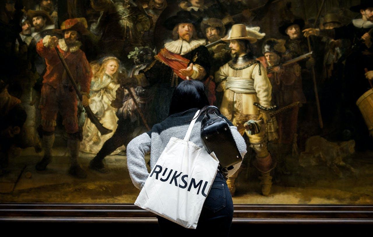 AMSTERDAM - Een bezoeker bekijkt De Nachtwacht tijdens de persvoorbezichtiging in het Rijksmuseum. ANP KOEN VAN WEEL