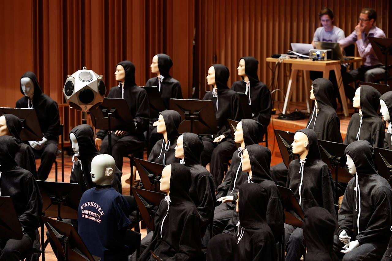 Onderzoek in het Muziekgebouw Frits Philips, waarbij Remy Wenmaekers en Antoine Weber aangeklede etalagepoppen gebruiken als stand-ins voor een orkest.