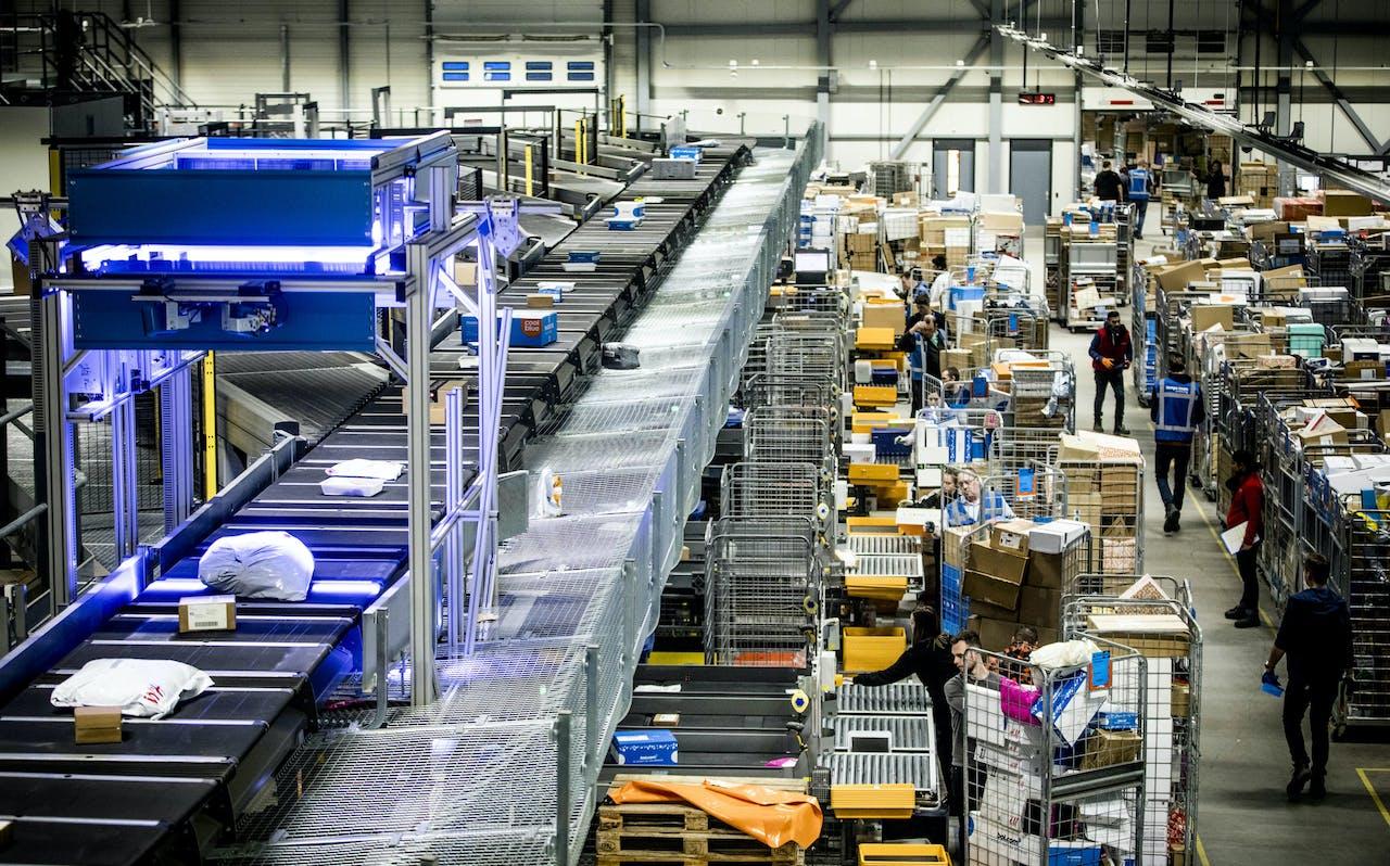 Medewerkers van PostNL sorteren pakketjes in het pakkettensorteercentrum. ANP FREEK VAN DEN BERGH