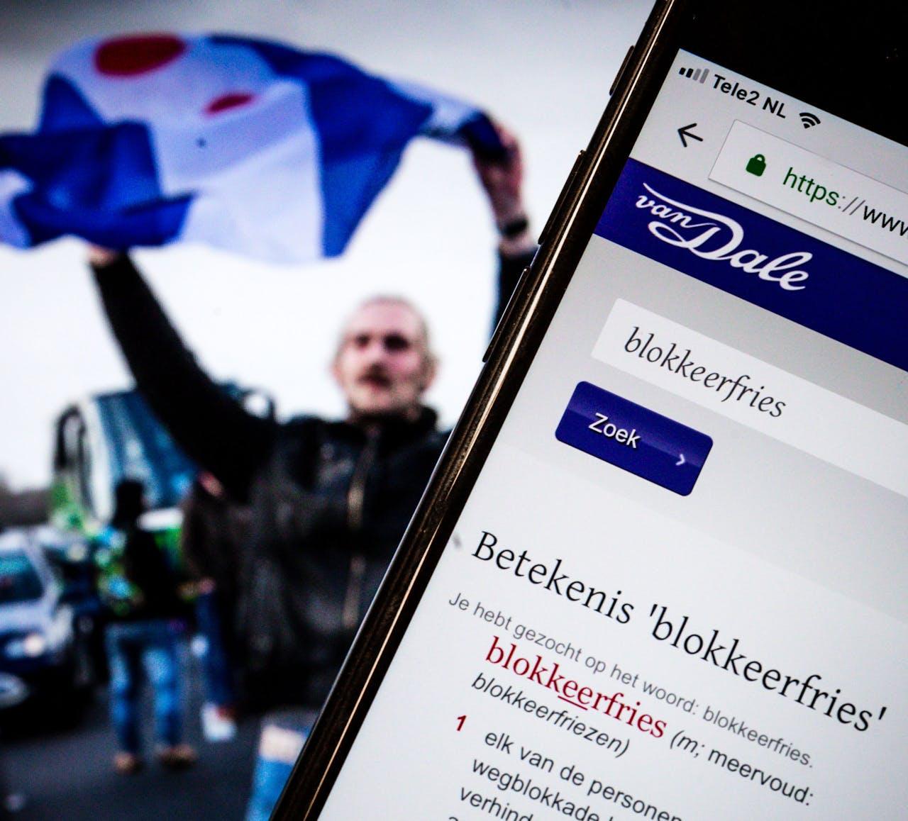 """Het online Van Dale op een telefoon. De uitgever van het woordenboek heeft het woord """"Blokkeerfries"""" uitgeroepen tot woord van het 2018."""