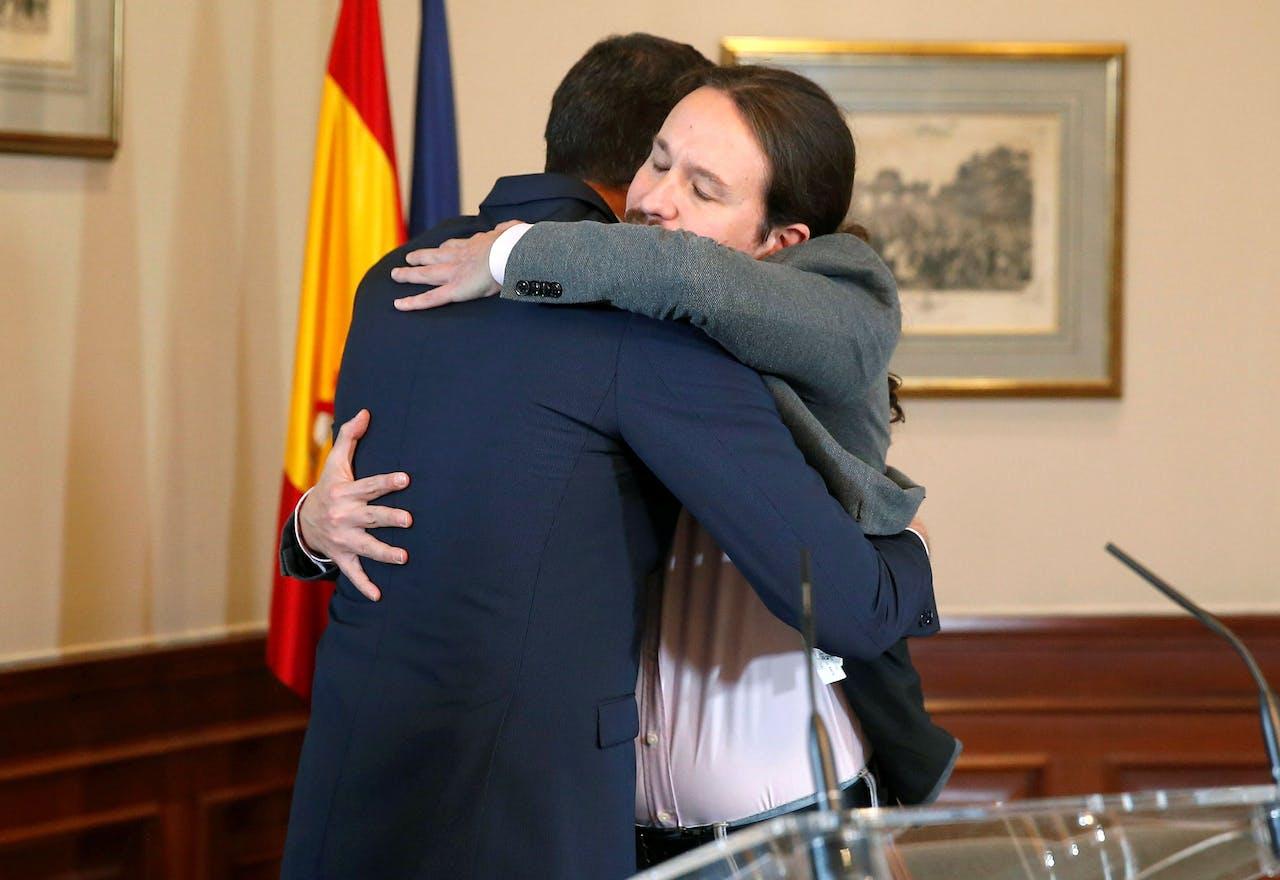 Spaanse premier Pedro Sanchez en de leider van Podemos Pablo Iglesias omarmen elkaar nadat zij een coalitie hebben aangekondigd.