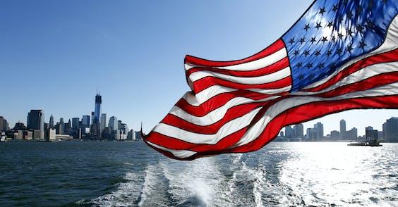 De skyline van Manhattan (L) en New Jersey (R) gezien vanaf de Hudson River met vlag in New York, de Verenigde Staten van Amerika.