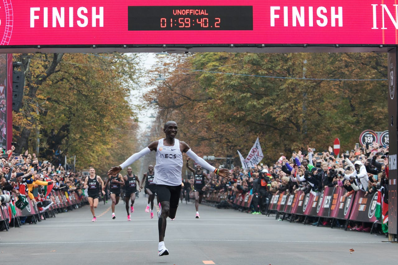 2019-10-12 12:28:37 (FILES) In this file photo taken on October 12, 2019 Kenya's Eliud Kipchoge (white jersey) celebrates as he crosses the finish line at the end of his attempt to bust the mythical two-hour barrier for the marathon in Prater Park, Vienna, with an unofficial time of 1hr 59min 40.2sec. ALEX HALADA / AFP