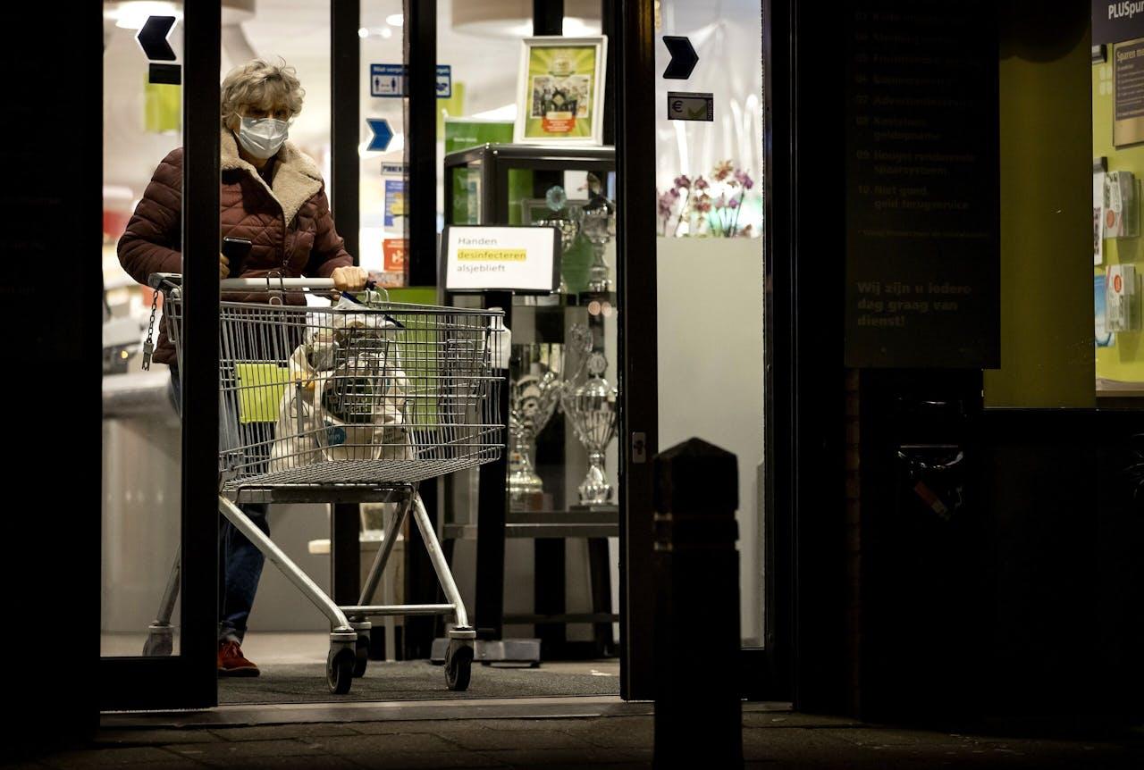 2021-01-22 18:22:51 OOSTHUIZEN - Klanten in een PLUS supermarkt. Bij invoering van een avondklok moeten de supermarkten die tot laat open zijn de deuren eerder sluiten. ANP KOEN VAN WEEL